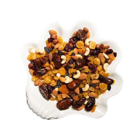 Mix of nuts and berries: raisins, hazelnut, cashews, almonds, cranberries, dried dates and apricots. Plate of dried fruits on white, isolated on white background with clipping path, flat lay.