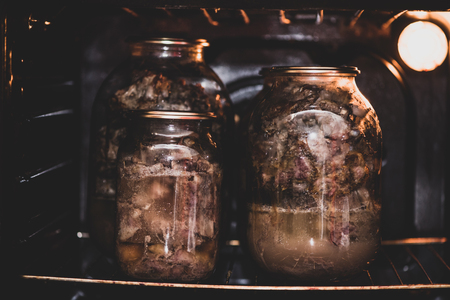 Glass jars with a stewed pork in hot oven. Homemade cooking with a traditional recipe. Matte toning technique.