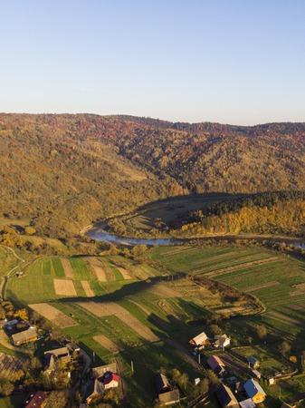 Aerial Drone Blick auf die Berge im Herbst mit Wäldern und Fluss, Wiesen und Hügeln im weichen Licht des Sonnenuntergangs. Karpaten, Ukraine