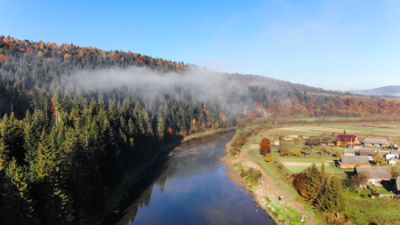 Over the mountain river Stryi, aerial view. Beautiful autumn nature in Carpathians, Ukraine