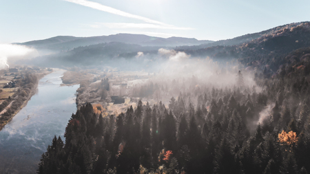Autumn landscape in Carpathian Mountains. River, hills and coniferous forests on the slopes. Morning time.