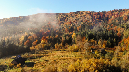 Old wooden huts in the valley of Carpathian Mountains, autumn landscape, morning time