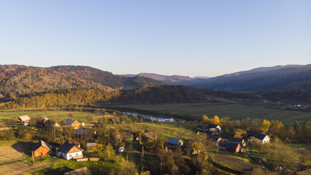 Aerial Drone View of autumn mountains with forests and river, meadows and hills in sunset soft light. Carpathian Mountains, Ukraine Stock Photo