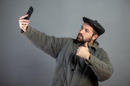 Caucasian man 35 years old doing selfie, studio shot. Idea - village dweller and modern technology, set