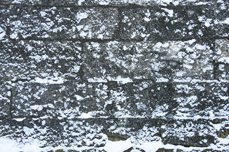 Medieval stone wall is covered with snow, design background with copy space for text