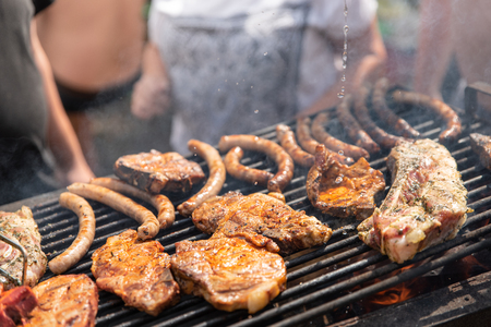 Barbecue, process of cooking meat. Rest on weekends. Friends on a picnic.