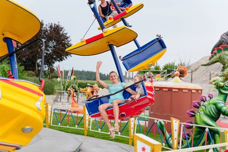 Loifling, Germany - 26 July, 2018: Mom and her daughter are having fun on the Star fly carousel in Churpfalzpark Loifling amusement park.