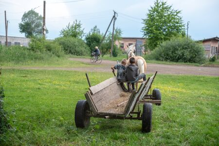 Litynia village, Ukraine - June 02, 2018: Two young boys riding on an old wooden cart. Life in a village, lifestyle Editorial