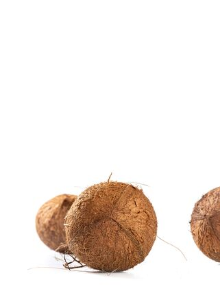 Three hairy coconuts on white background, with copy space