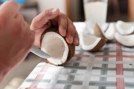 Man cut fresh coconut into pieces, process close up. Exotic food