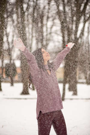 Young beautiful woman is enjoying the snow scattering it in the air, positive emotions, joy and happiness. Winter fun outdoors. Фото со стока