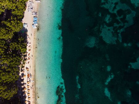 Aerial view of turquoise water of Balearic sea and green nature at Formentor beach, Palma de Mallorca island, Spain. People relax on the beach. Summertime, time to travel, relax and wellness.