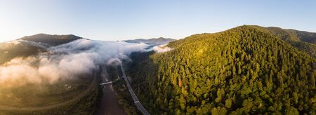 Aerial view above misty mountains and forest. Panoramic landscape. Morning time. Carpathians, Ukraine