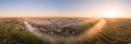 Aerial view of traditional Ukrainian village at sunset. Wide angle panoramic landscape of rural area. Early autumn. Smoke spreads through the village. Ripchytsi village, Ukraine. Stockfoto