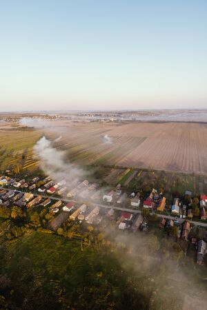 Aerial view of traditional Ukrainian village. Smoke spreads through the village. Early autumn, sunset Stockfoto