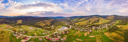 Aerial drone view of urban village Pidbuzh in Carpathians, Ukraine. 180 degrees panoramic landscape of rural area. Sunset time, end of summer Stockfoto