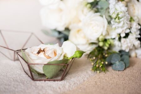 Two wedding rings in beautiful box and bouquet of flowers. Themes of engagement, declaration of love, wedding day, florist services. Reklamní fotografie