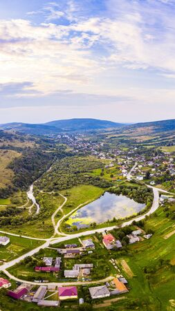 Vertical landscape of settlement in valley between mountains. Sunset time, end of summer. Aerial drone view of urban village Pidbuzh in Carpathians, Ukraine.