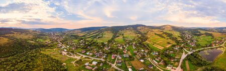 180 degrees panoramic landscape of countryside, aerial drone view of urban village Pidbuzh in Carpathians, Ukraine. Sunset time, end of summer.