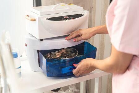 Cosmetologist puts the manicure tools in High Temperature Sterilizer. Cleanliness and disinfection. Beauty salon. Stockfoto