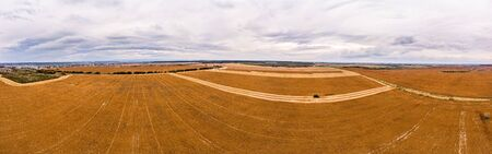 Aerial drone view of farmland. Combines work in the agricultural lands, harvesting. 180 degrees panoramic landscape.