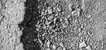 Broken road with potholes, asphalt surface destroyed. Bad road condition that needs repair. Banner size, top view. Monochrome toning
