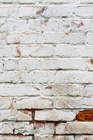 Old wall, cracked and dirty, bricks. White color vertical design background.