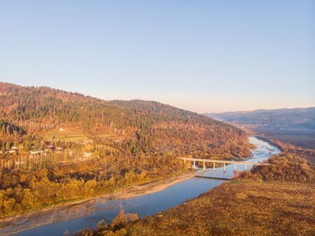 Beautiful sunny autumn morning between nature, mountains and forests. Bridge crosses river