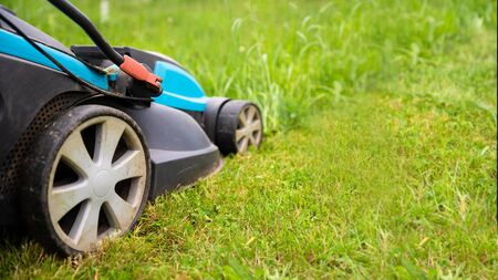 Electric lawn mower machine in garden on grass. Garden and lawn care theme. Banner format with copyspace
