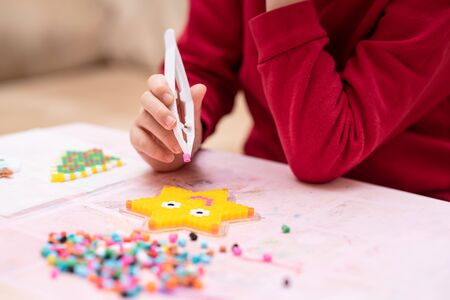 Little girl holds a tweezers with bead, creates art toy from fusible colorful beads, last touches. Also known as perler beads. Toy that develops the imagination of child. Process close-up