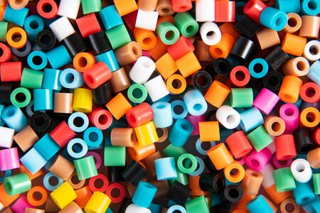 Set of multicolor fusible perler beads close up, top view. Kids toy that develops the imagination of child. Theme of leisure, hobby and development. Imagens