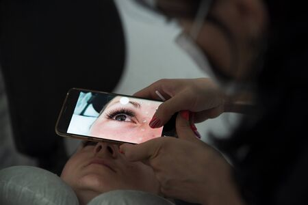 Cosmetologist makes a photo using smartphone and fixes the result of work eyelash extension procedure in a beauty salon. Self-promotion and advertising of private business in social networks