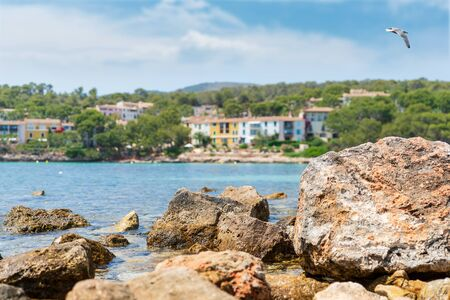 Rocky shore, blue transparent water of Mediterranean Sea, seagull in blue sky, hotels on the shore. Summer natural background with copy space. Playa de Illetas beach, Majorca, Balearic islands, Spain. Imagens