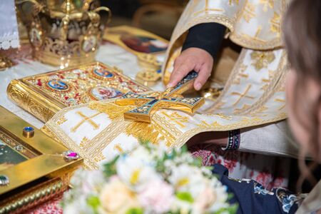 Priest is crowning a young couple in the temple. Sacrament of marriage. Promise of newlyweds in the church. Hands of young couple lie on the scripture and make vow, priest holds cross on their hands
