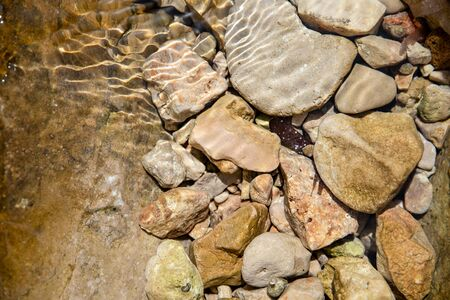 Stones in clear water, sun reflection, summer. Natural background, top view, close up. Imagens