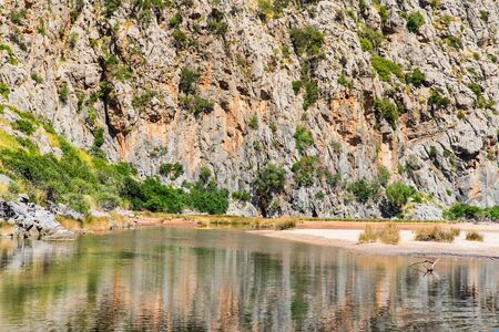 Beautiful rocky mountains with a river in valley, landscape of wildlife, summer. Nature in Mallorca, Balearic Islands, Spain. River Torrent de Pareis between rocky mountains. Imagens