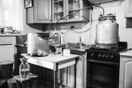 Old-fashioned moonshine machine for creating homemade strong alcohol in the kitchen. Process of distillation, general view. Story about an aged way of distilling moonshine at home. Monochrome effect. Imagens
