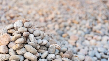 Heap of sea pebbles on a shore, close-up. Natural summer background with soft copy space. Summer time theme.