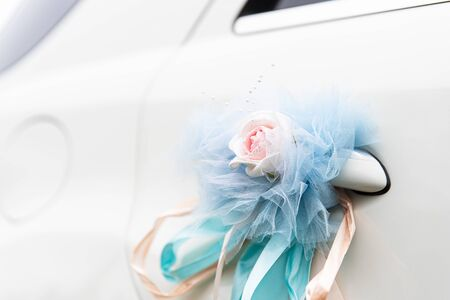 Artificial bouquet with ribbons attached to the door of a white car. Decoration on car door in wedding day. Services of organization of solemn and memorable events.