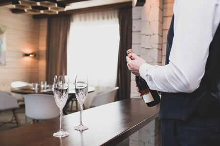Man opens a bottle of sparkling wine. Two glasses stand on bar counter. The action takes place inside the cozy hotel room.