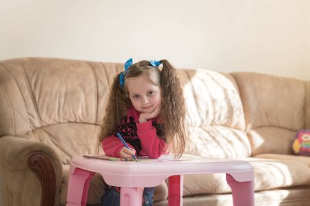 Cute little girl engages her favorite activity. Six years old caucasian girl holds a colored pencil and looks into the camera. Themes of developing talents child, leisure and hobby.