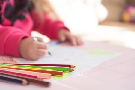 Color pencils lying on the table. Process of drawing by a little child, close up view. Soft background with copy space. Themes of child development, leisure and hobby. Archivio Fotografico
