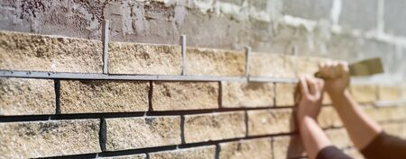 Wall cladding. Decorative bricks with rocky relief surface. Wide-angle background with copy space, angle view Archivio Fotografico