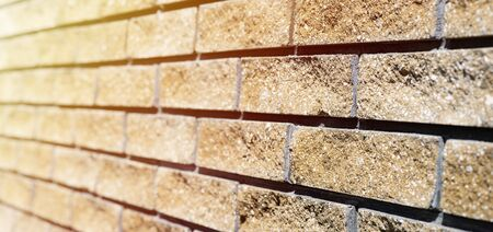 Wall cladding. Decorative bricks with rocky relief surface. Wide-angle background with copy space, angle view Фото со стока
