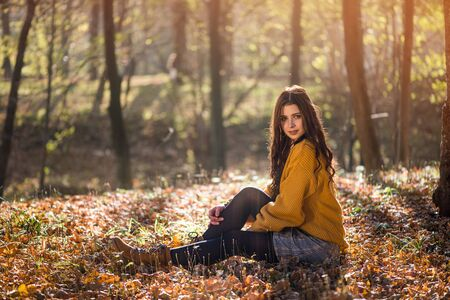 Young beautiful caucasian woman sits on the ground in a autumn park among high trees. Mysterious and seductive look of a beautiful woman. Archivio Fotografico