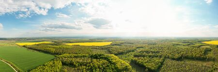 Scenic landscape of countryside from bird's eye view, springtime. Aerial drone view of woodland and farmland.