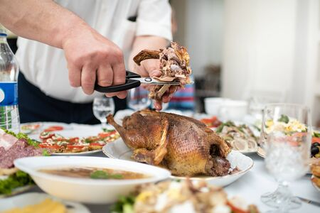 Man divides with scissors freshly baked duck into portions, process close up. Events take place at home during a family meeting to celebrate the solemn event. Foods and dishes on a table