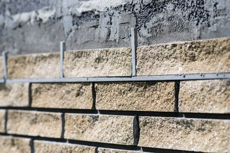 Wall cladding, angle view, process close up. Decorative bricks with rocky relief surface. Фото со стока
