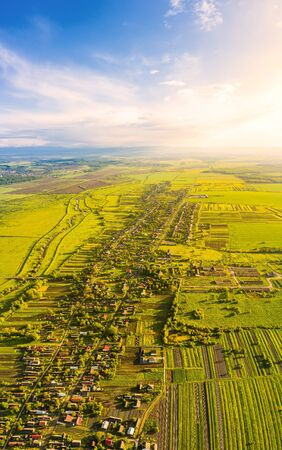 Scenic aerial drone view of countryside. Soft sunlight illuminates blue sky, green meadows and village. Vertical panoramic landscape from birds-eye view