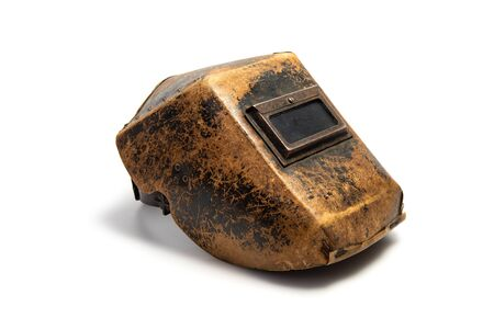 Aged welding mask with traces of wear isolated on white background. Favorite mask of the master with whom he did not part for thirty years. Quality is time-tested.